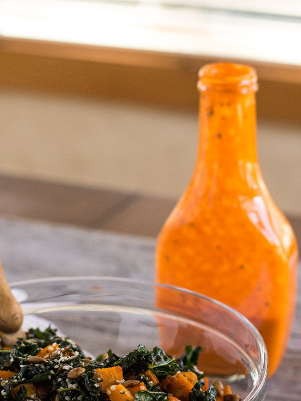 Roasted Red Pepper Vinaigrette in salad dressing bottle with bowl of kale and squash salad