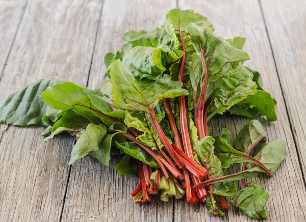leafy red chard with stems on wood table