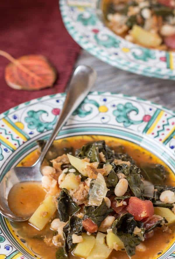 Portuguese Kale and Potato Soup in bowls with autumn leaves