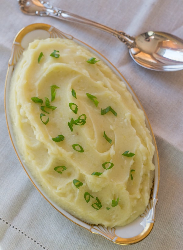 Roasted Garlic Mashed Potatoes in serving dish with green onion garnish
