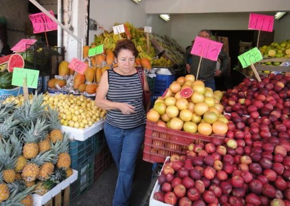 browsing fruit and vegetable stall for Poblano chiles with potatoes and cheese