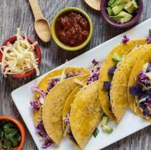 Purple Potato and Bean Tacos arrange on white plate with condiments on the side