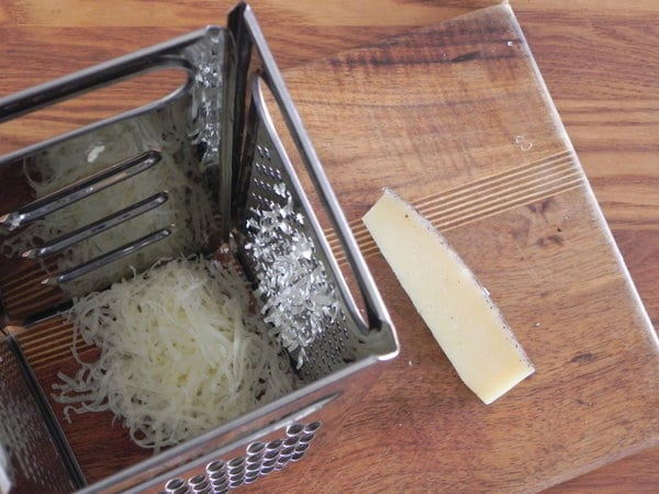 grating Manchego cheese for Garlic and Rice Soup