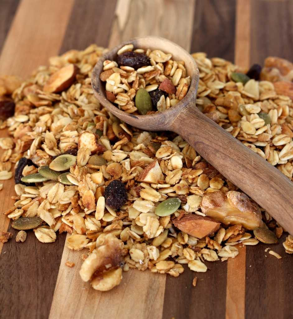 granola on a board with wooden spoon