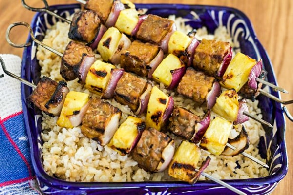 Tempeh and Pineapple Kebabs with Peanut Satay Sauce in blue dish with rice