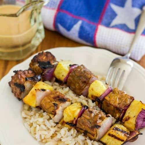 Tempeh and Pineapple Kebabs on top of rice with Satay sauce on the side