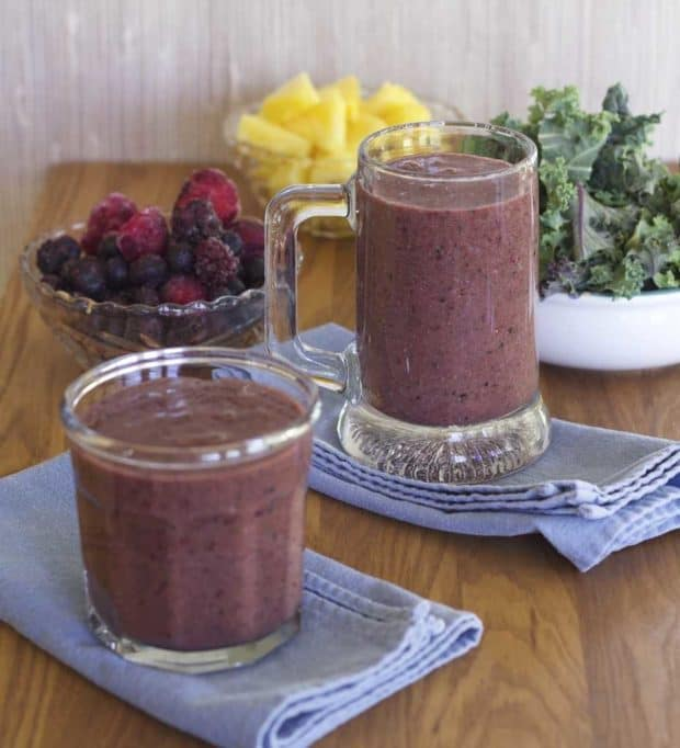 Two Triple Berry Kale Smoothies in mug and glass with fruit and kale in background