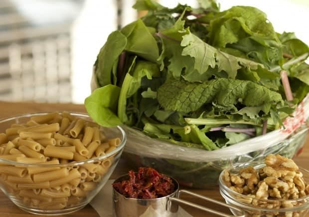 Greens, pasta, dried tomatoes and walnuts, the ingredients for Penne Pasta with Mixed Greens
