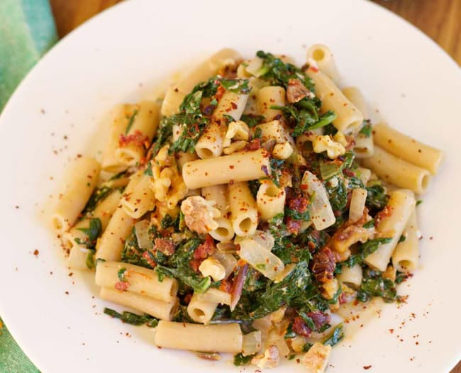 Penne Pasta with Leafy greens on white plate horizontal shot