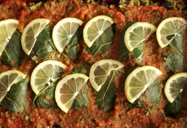Collard Rolls with Rice Pilaf ready to bake, with tomato sauce and lemon slices.