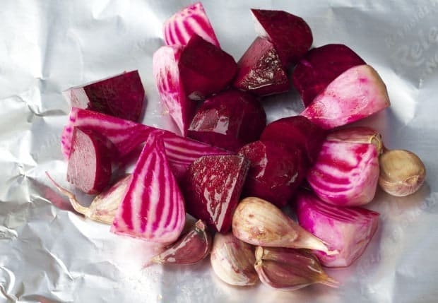 Beet wedges and Garlic cloves on sheet of aluminum foil