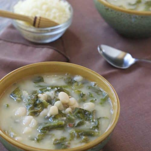 Escarole and White Bean Soup in bowls on brown napkins with bowl of Parmesan cheese in background