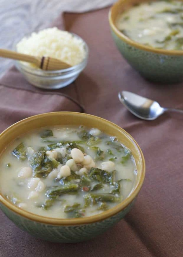 Escarole and White Bean Soup in bowls on brown napkins with bowl of Parmesan cheese in backgroundb