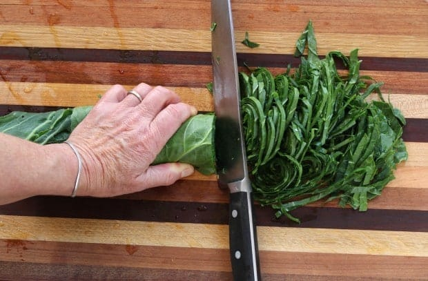 cutting collard leaves into thin ribbons for Dirty Rice with Collards and Leeks