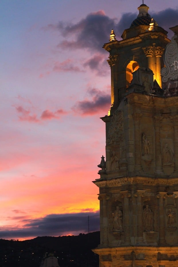 Oaxaca at sunset with church in foreground, the Basilica de la Soledad.