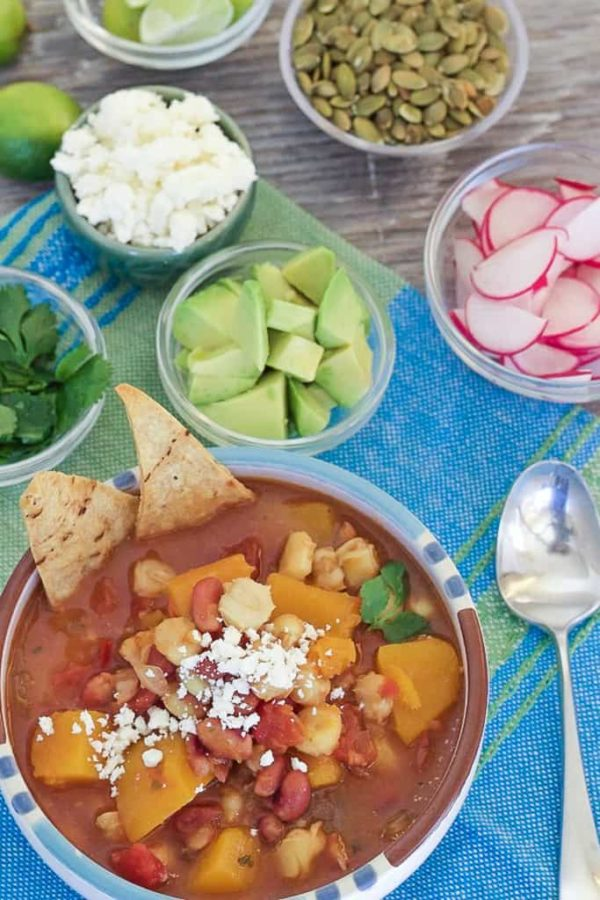 Easy one-pot Slow Cooker Butternut Squash Posole made with dried chiles, hominy and pinto beans. Garnish with cotija cheese, avocado and cilantro.