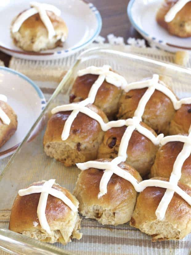 Gingery Hot Cross Buns in pan ready to eat with a few on plates