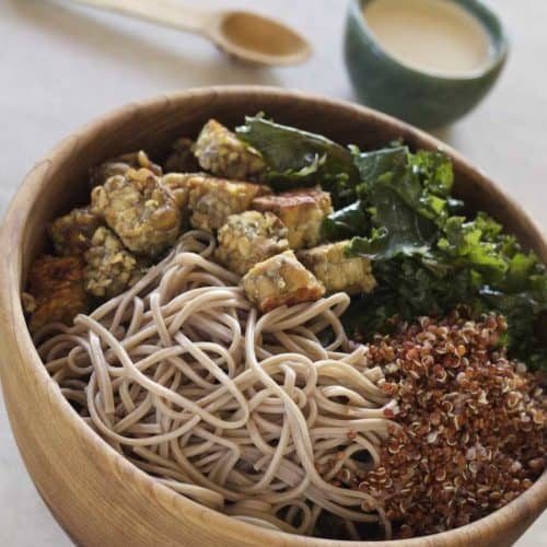 Soba Noodles, Kale, Tempeh and quinoa in a wooden bowl with Tahini Sauce on the side