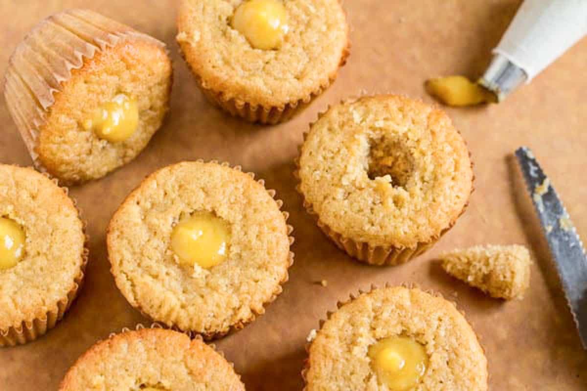 piping lemon curd into cupcakes
