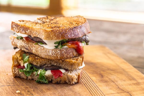 Roasted Portobello, Red Pepper, Arugula and Mozzarella Grilled Cheese on cutting board
