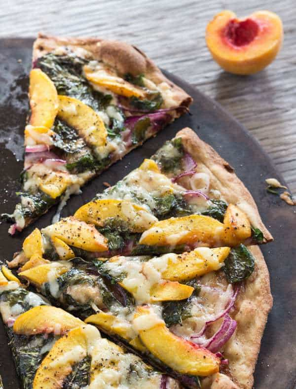 Peach and Arugula Pizza cut, on pizza stone