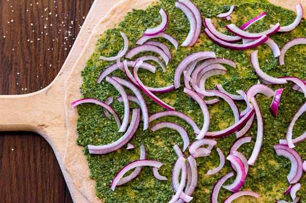 pizza dough on wooden board spread with pesto and onion slivers