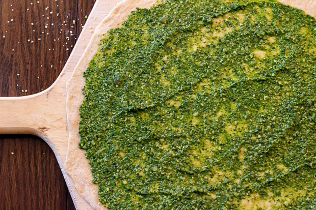 pizza dough on wooden board spread with pesto