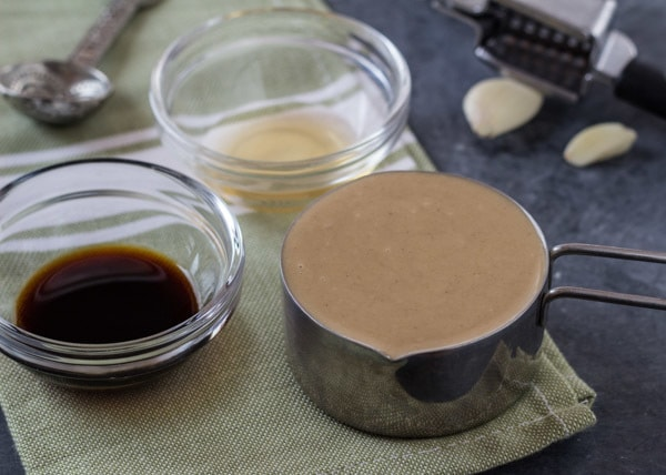 Tahini, tamari and vinegar in bowls--the ingredients for Tamari Tahini Sauce
