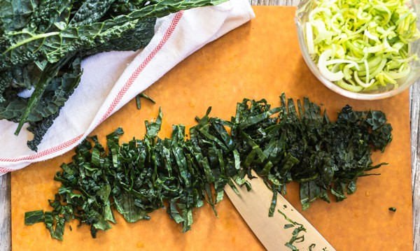 cutting kale ribbons for Healthy Paprika Kale, Baked Tofu and Almonds | Letty's Kitchen