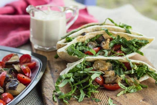 Roasted Eggplant and Tomato Pitas with Lemon Tahini Sauce on the side in a little glass pitcher