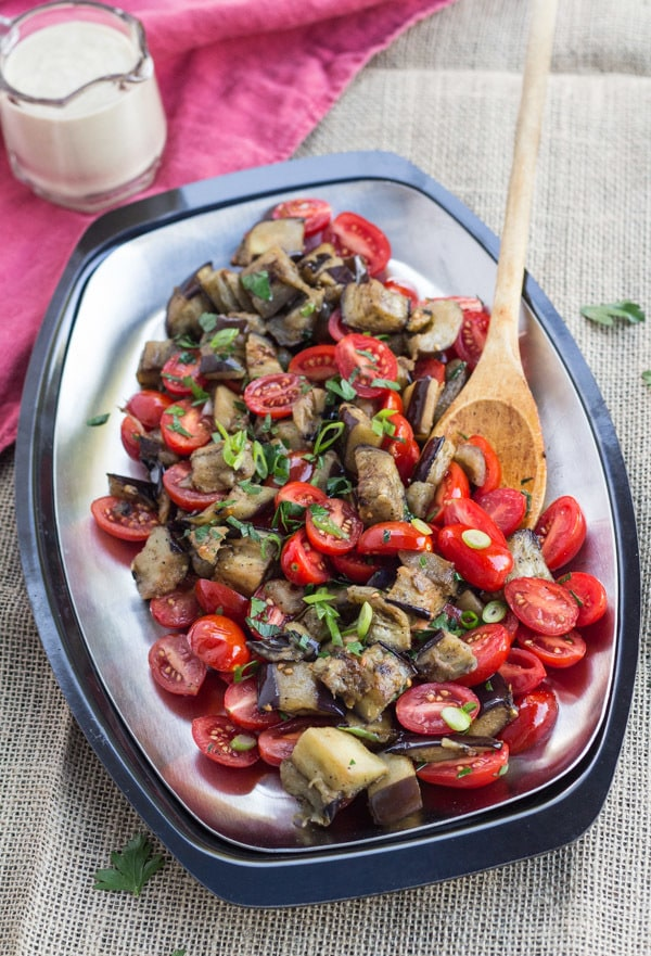 Roasted Eggplant and Tomatoes on a plate with a pitcher of Lemon Tahini Sauce