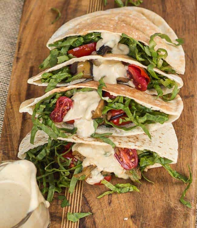 Eggplant and tomato pita pockets with lemon tahini sauce, arranged on wooden board