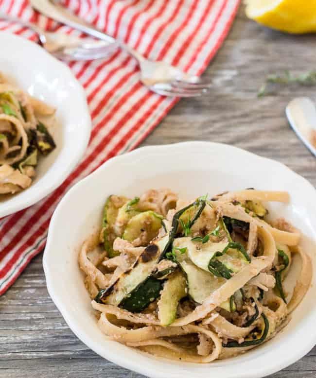 zucchini and fettuccine and walnut pesto in white bowl