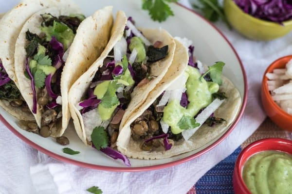 Greens and Lentil Tacos on a plate, with Guacamole Sauce and jicama and cabbage on the side.