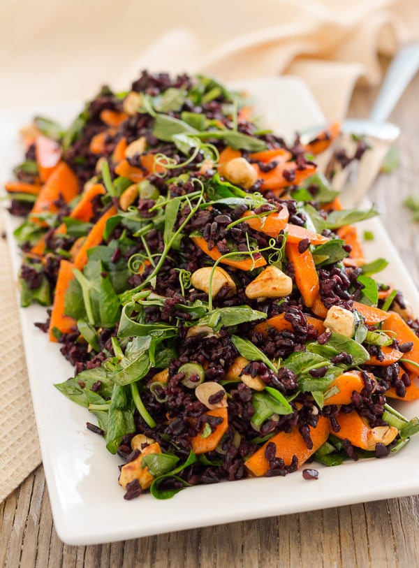 Black Rice and Pea Shoot Salad on a white rectangle plate, ready to serve
