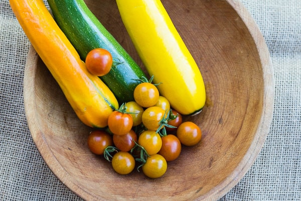 zucchini and cherry tomatoes fin wooden bowl