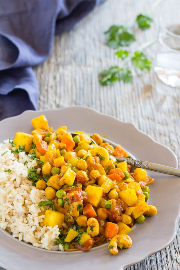 Potato Chickpea Curry on plate with rice with blue napkin