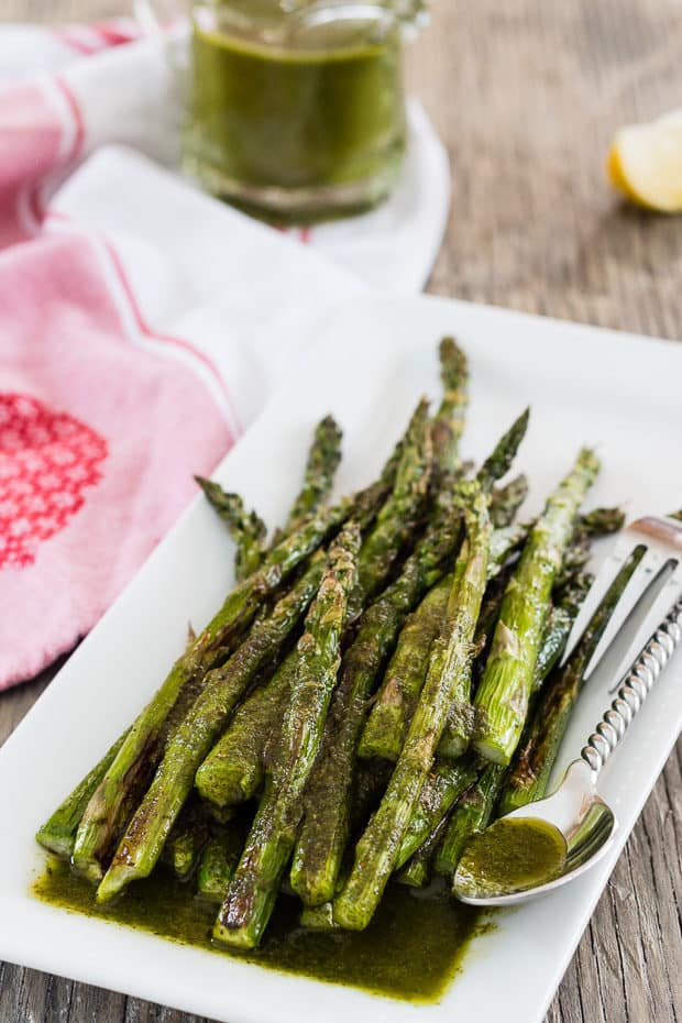 Roasted Asparagus with Cilantro Chimichurri Sauce on white platter with glass pitcher of sauce