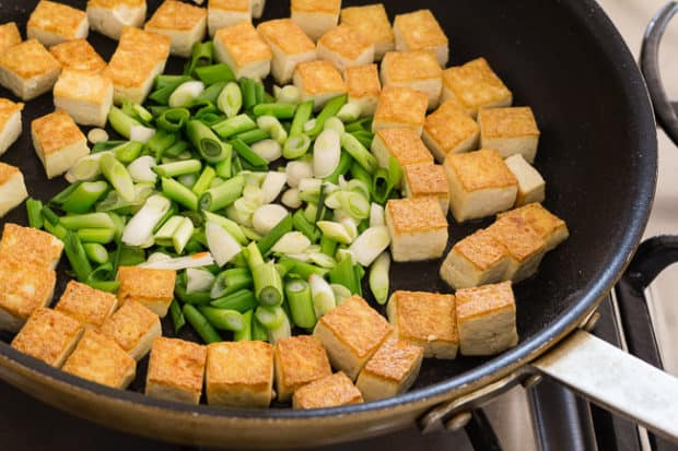 Golden tofu and green onions in skillet for Thai Peanut Noodles with Golden Tofu