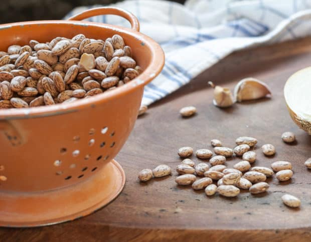 dried pinto beans in orange colander