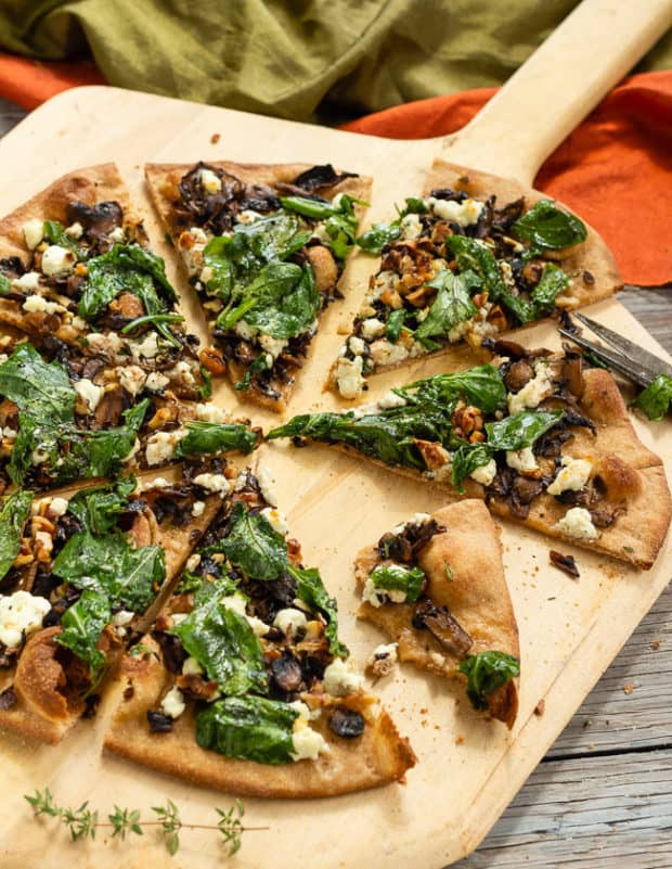 Caramelized Mushroom and Arugula Pizza Bianca cut with one slice half eaten