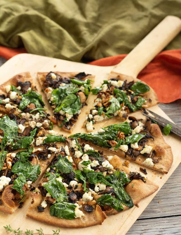 Caramelized Mushroom and Arugula Pizza Bianca cut, on wooden pizza peel