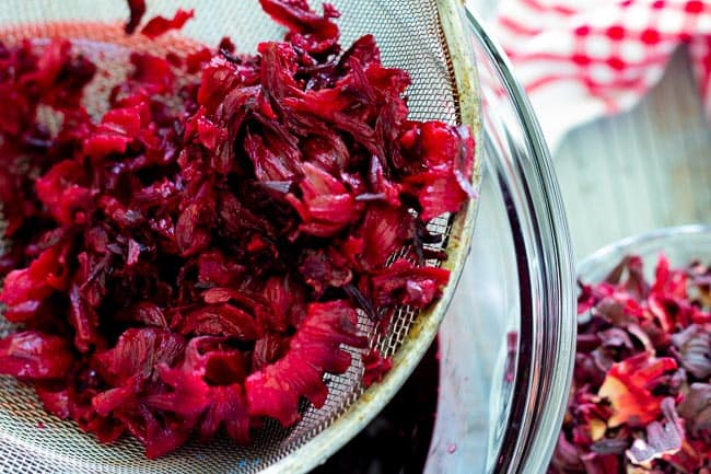 soaked and strained hibiscus flowers in strainer