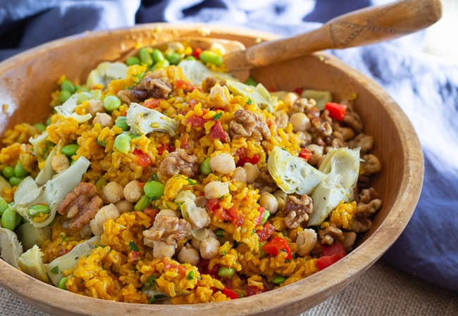 Brown rice paella salad in a bowl with artichoke hearts, saffron, chickpeas