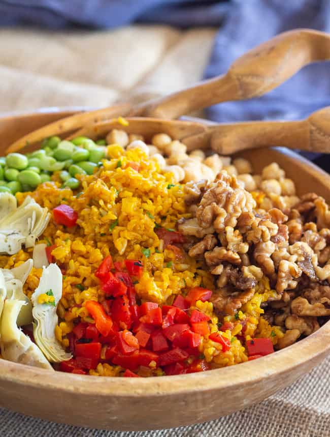 wooden bowl of saffron brown rice with spiced walnuts, chickpeas, edamame and artichoke hearts