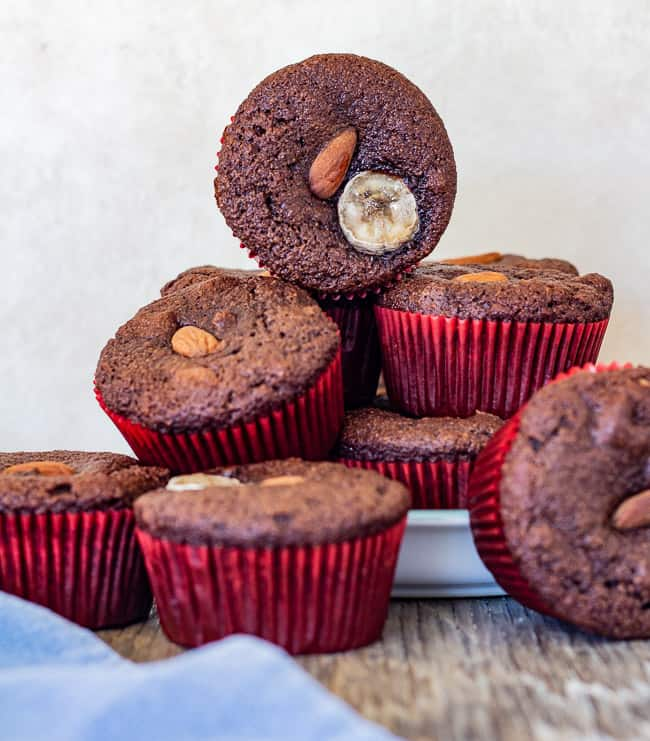 almond flour banana chocolate muffins stacked on plate with one facing camera