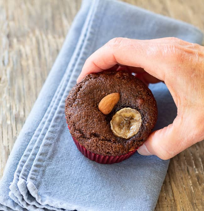 one almond flour chocolate banana muffin held in hand on blue napkin