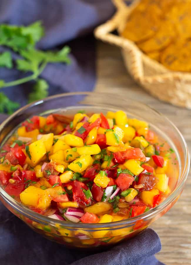 Peach and tomato salsa in glass bowl with basket of chips in back