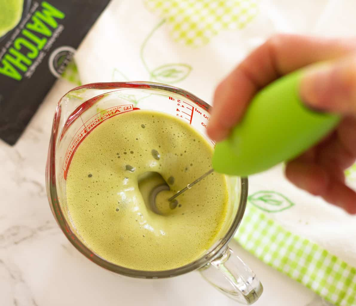foaming matcha latte in a measuring cup using a green handheld milk frother.